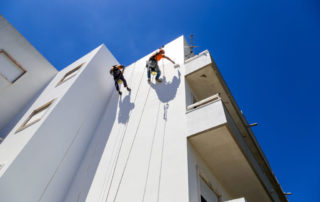 Industrial Alpinist Work On White Wall